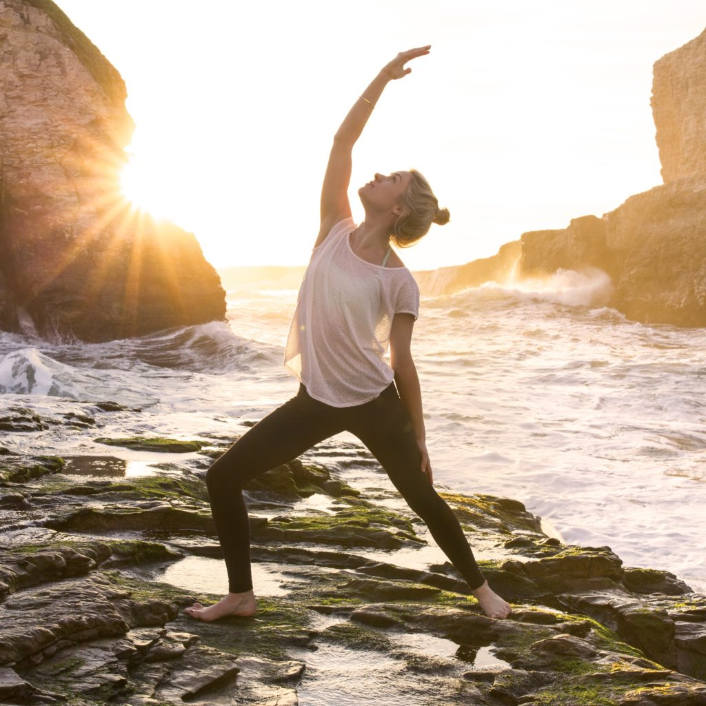 Young woman with CF strikes a yoga pose as waves break behind her.
