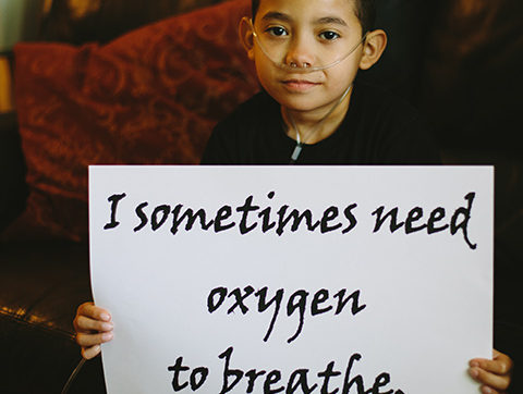 """A boy with oxygen supply tube holding a sign saying """"I sometimes need oxygen to breathe."""""""